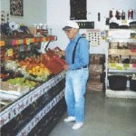 elderly man buys buying produce at grocers